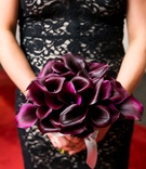 bridesmaid in black lace gown with white underlay holding a bouquet of deep purple calla lilies