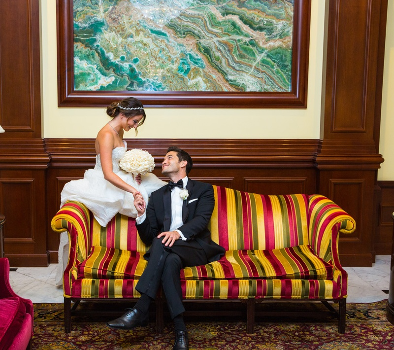 Bride and groom on colorful striped couch at Four Seasons Westlake Village