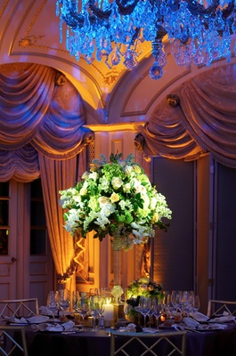 Blue chandelier over formal ballroom wedding table