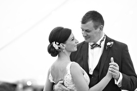 Black and white photo of bride with an updo and floral headpiece dance with groom in suit, plaid bow