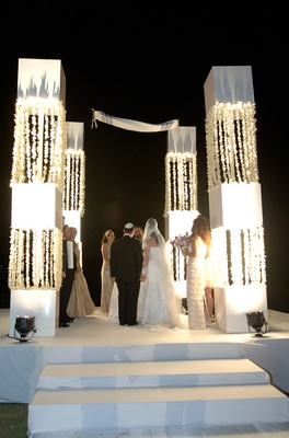 Bride and groom under large white chuppah