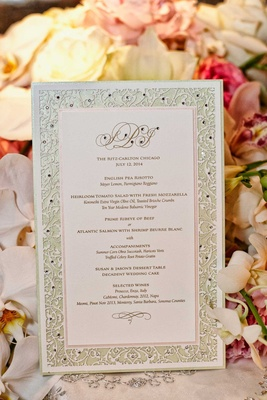 Wedding reception menu with laser-cut border sprinkled with rhinestones, couple's monogram