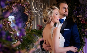 bride with wavy blonde hair in updo, open back and beaded straps, groom in navy tuxedo