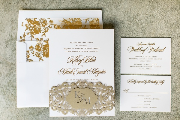 white invitation suite with gold writing, gold floral print envelope liner, champagne laser-cut band