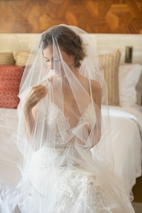 wedding portrait bride getting ready on bed berta wedding dress bridal veil over face tulle