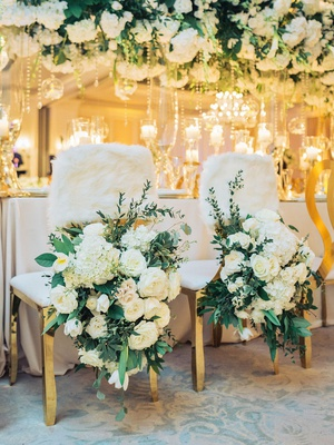 wedding reception head table bride groom chairs white flowers greenery faux fur wrap chair cover
