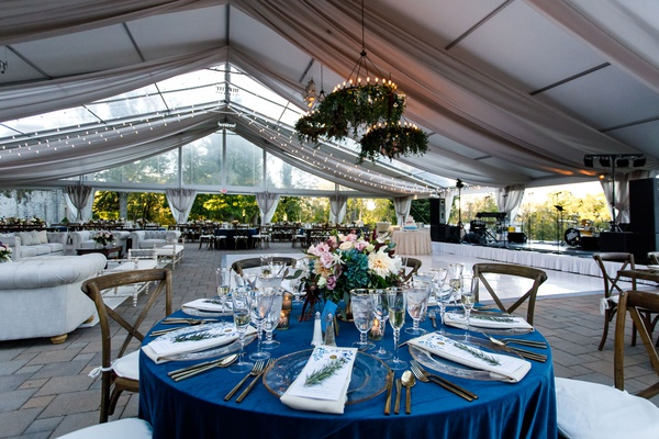 wedding reception tent flower chandeliers lounge area long wood tables round table blue linen wood