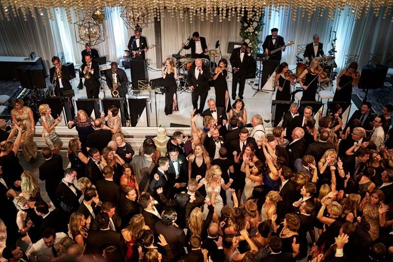 Wedding reception live band bride groom guests dancing on dance floor modern wedding entertainment
