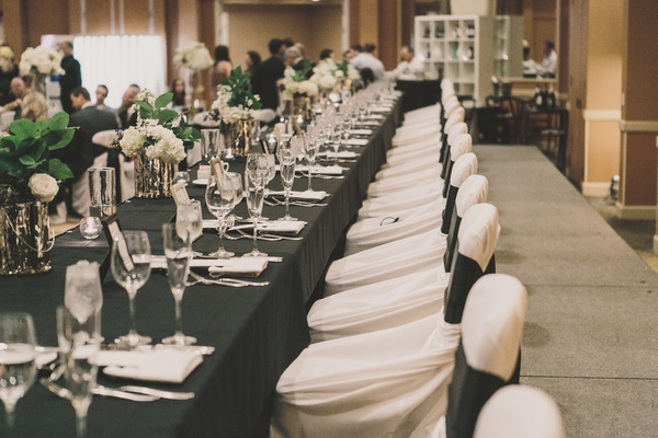 Long head table surrounded by black and white chairs