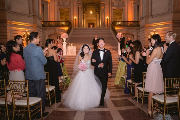 Bride in a strapless Kenneth Pool dress with embroidered bodice, tulle skirt, groom in black tux
