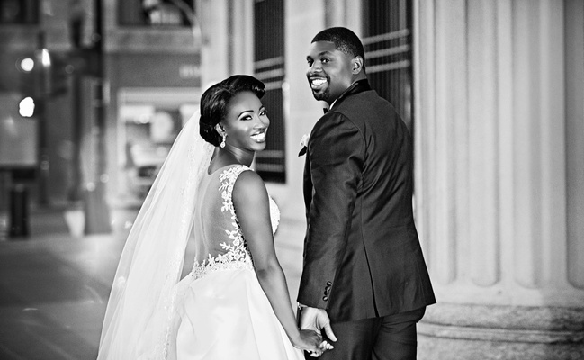 Black and white photo of African American couple getting married in Chicago bride in illusion back