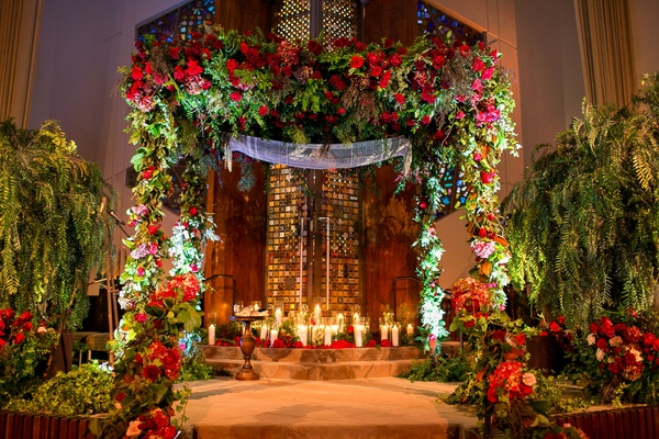 Temple Jewish wedding with lush greenery and red burgundy flowers at chuppah and ceremony stage