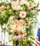 ceremony arch with amaranthus, peach, blush, and ivory flowers, heavy greenery, birch branched