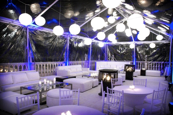 Clear tent with white lanterns and furniture