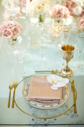 clear gold-rimmed charger, dusty rose napkin, white orchid, gold goblet