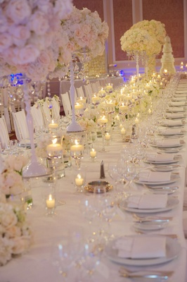 Floating candles and white flower centerpieces on reception table