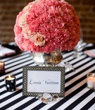Framed table name and pink centerpiece
