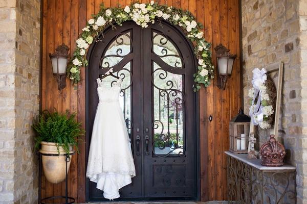 Nardos Imam wedding dress hanging from wrought iron door of Villa Bianco in Texas