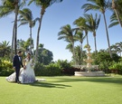 bride in purple floral romona keveža wedding dress, groom in navy tuxedo, palm trees