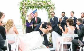 bride in allure ball gown, groom in navy joseph abboud suit, dipped for first kiss as husband wife