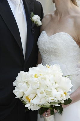 Bride holding all white wedding flowers with white tulips
