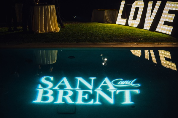 blue light projection of the couples' names, custom lighting