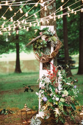 Outdoor wedding reception with a branch wreath with leaves, feathers, and flowers against a tree