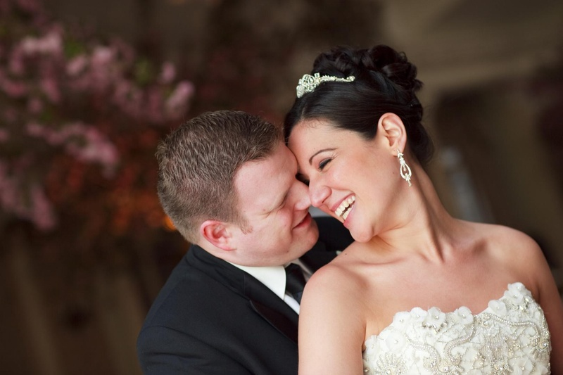 Bride with an updo and tiara and groom in a black tuxedo