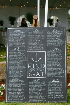 Large chalkboard wedding reception seating chart with names listed in alphabetical order