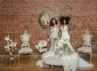 two model brides in pantora bridal wedding dresses in vintage-inspired lounge area