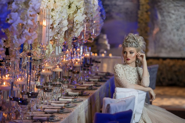 Bride with large headpiece and beaded dress sitting at white chair cover long table styled shoot