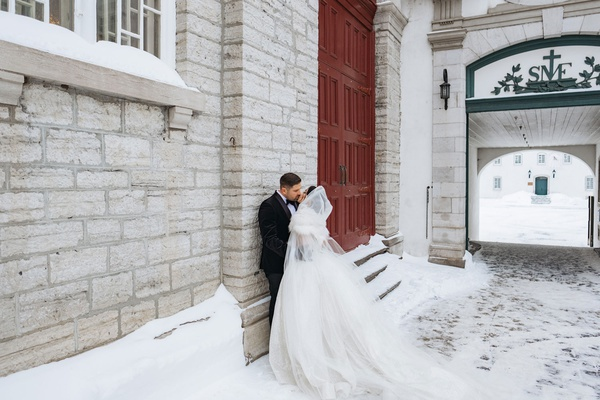 wedding portrait bride and groom outside winter wedding quebec city canada stone building tall doors