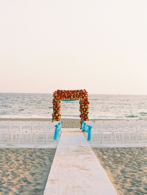 Beach wedding ceremony in Malibu blue turquoise ribbon and flower arch of red and yellow blooms