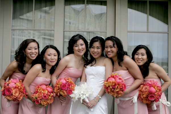 Bride in a Vera Wang gown with bridesmaids in strapless pink dresses