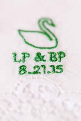 Green swan embroidery on white handkerchief with wedding date, initials, and swan