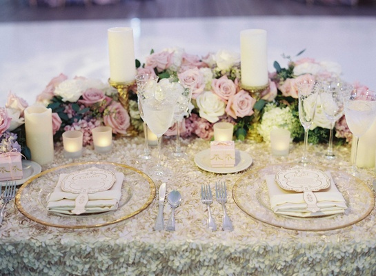 Wedding reception sweetheart table with fabric flower tablecloth, pink and purple flowers