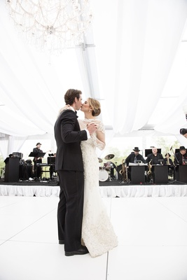 bride groom kiss while dancing wedding reception all white black tux love newlyweds