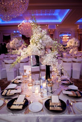 Wedding reception table with tall mirrored vases and white flowers, silver beaded rimmed chargers