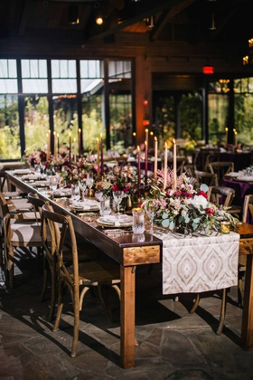 rustic old-europe themed banquet tablescape with dark candles and sage greenery wine colored flowers