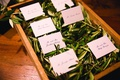 shallow wooden box filled with olive leaves with escort cards on top