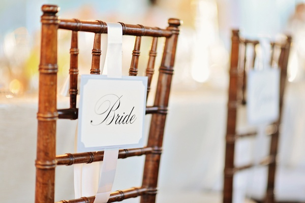 Wooden chairs with bride and groom seat signs