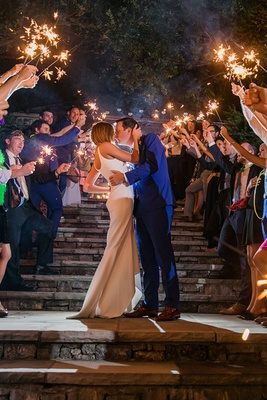 bride in wedding dress groom in blue suit guests holding sparklers on staircase stone