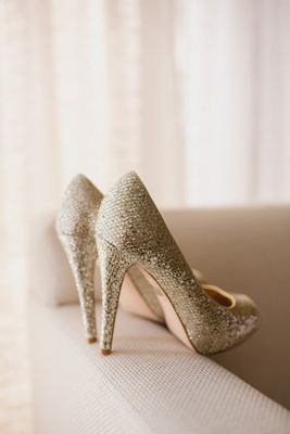 Gold metallic Badgley Mischka wedding shoes on ivory couch arm