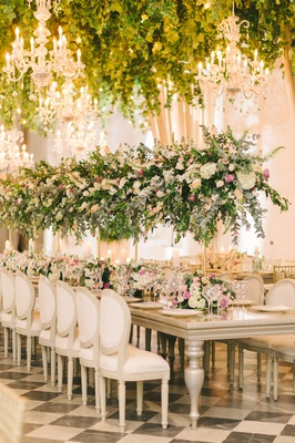 wedding reception checkerboard floor white chairs tables tall centerpiece greenery chandelier