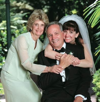 Father of the bride gets hug from bride and wife