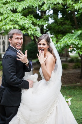 a newlywed couple excitedly showing off their new bands after their church ceremony