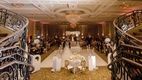 wedding reception ballroom white dance floor flowers gold metallic chairs chandelier staircase