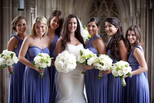 Bride with bridesmaids in mismatched purple dresses