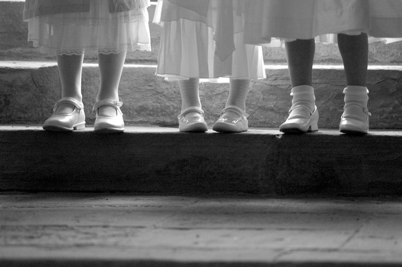 Black and white image of three flower girls on step with just shoes and socks showing