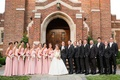 Bride and groom in front of church with bridesmaids and groomsmen